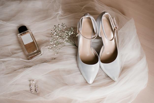 Bruidstoebehoren: schoenen, eau de toilette of parfum, oorbellen en een takje gypsophila-bloemen op tule