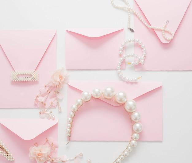 Bruiloft achtergrond, versierd met roze uitnodigingen en parel sieraden
