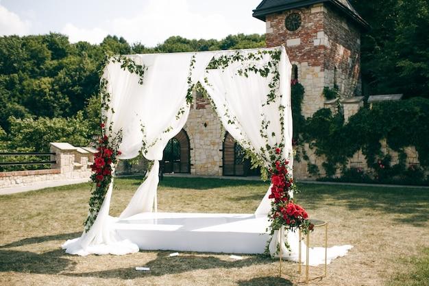 Bruiloft altaar gemaakt van vierkante gordijnen staat op de achtertuin
