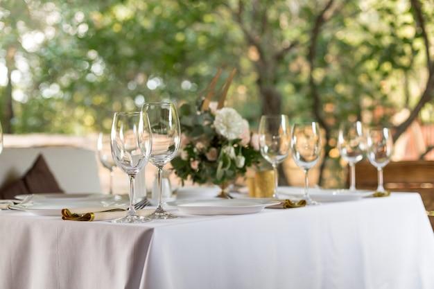 Bruiloft banket tafel voor gasten buitenshuis met uitzicht op de groene natuur