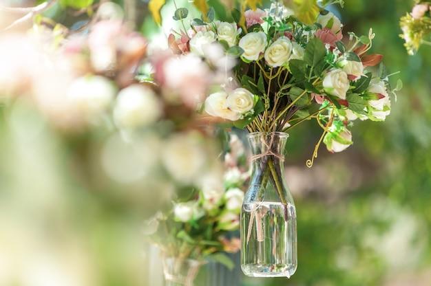 Bruiloft bloemdecoratie in de vorm van een kleine transparante vaas