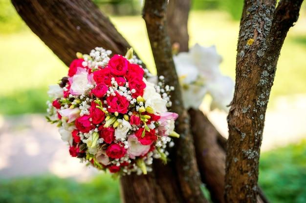 Bruiloft bloemen concept. het boeket van de bruid op een boomachtergrond. felle kleuren. detailopname.