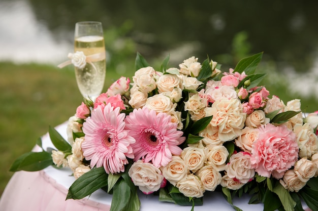 Bruiloft bloemen en champagne glas op tafel voor huwelijksceremonie