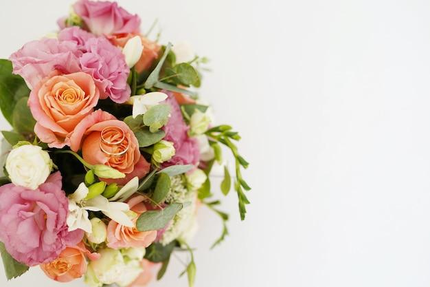 Bruiloft boeket bloemen en gouden ringen geïsoleerd