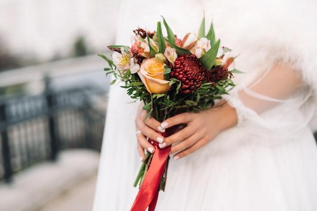 Bruiloft boeket in de handen van de bruid. het decor op de bruiloft.