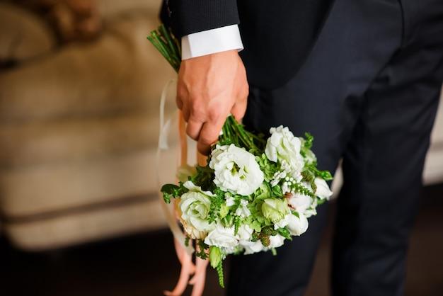 Bruiloft boeket in de handen van de bruidegom.