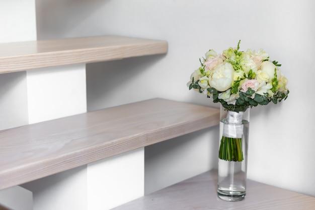 Bruiloft boeket in een glazen vaas op de trap in de buurt van de muur.