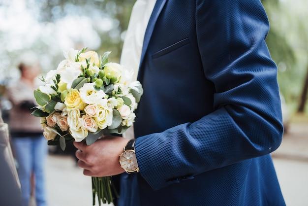 Bruiloft boeket in handen van de bruidegom