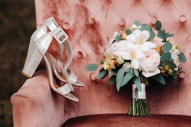 Bruiloft boeket met pioenrozen en rozen op een stoel en corsages. het decor op de bruiloft.