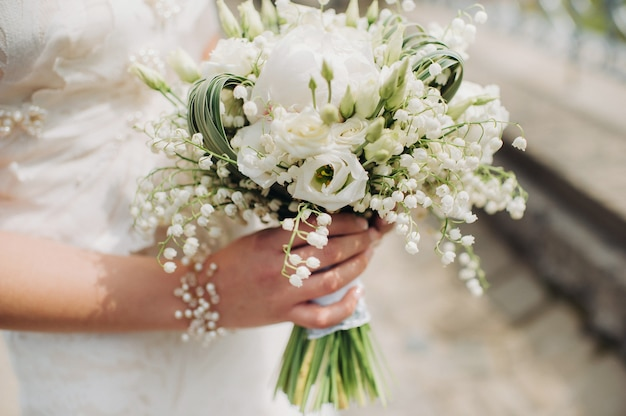 Bruiloft boeket met pioenrozen in de handen van de bruid onder de sluier ochtend van de bruid
