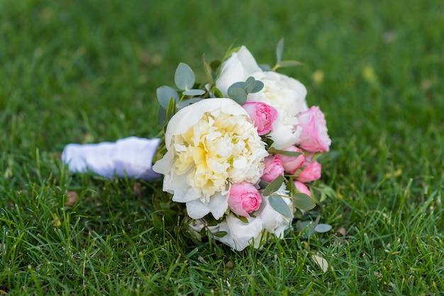 Bruiloft boeket met roze bloemen ligt op groen gras