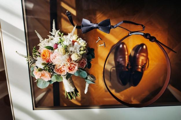Bruiloft boeket met rozen op tafel en een corsagesthe decor op de bruiloft