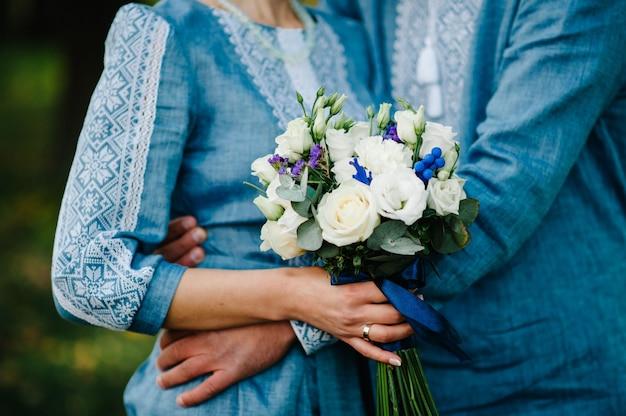 Bruiloft boeket op de achtergrond stijlvolle bruiden vrouw, gekleed in geborduurde jurk en bruidegom in shirt houdt een boeket. huwelijksceremonie. detailopname.