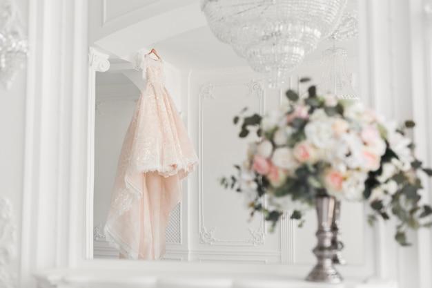 Bruiloft boeket op de achtergrond van een luxe trouwjurk op een hanger