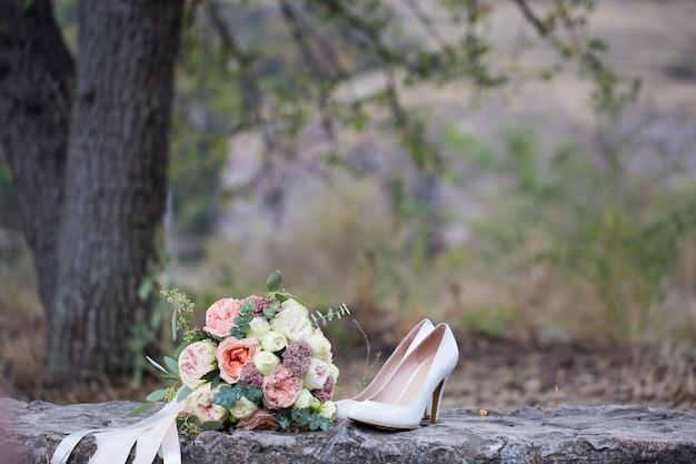 Bruiloft boeket rozen en schoenen close-up.