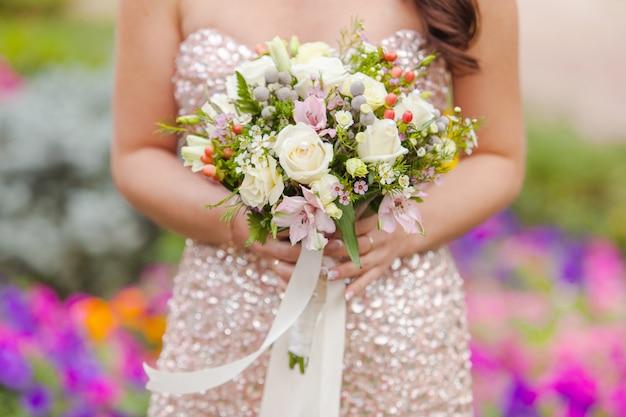 Bruiloft boeket rozen in de handen van de bruid