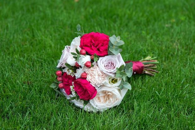 Bruiloft boeket van heldere rode bloemen op het gras