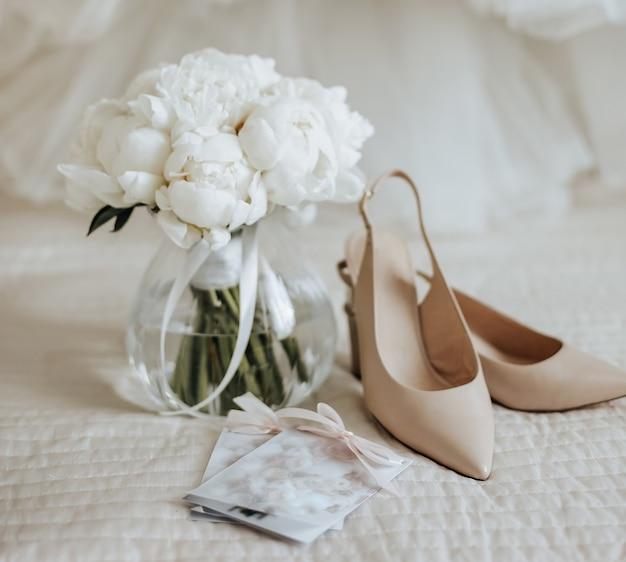 Bruiloft boeket van pioenrozen bloemen in een vaas staat op het bed van de pasgetrouwden met uitnodigingen en schoenen op de achtergrond van de bruid jurken