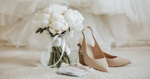 Bruiloft boeket van pioenrozen bloemen in een vaas staat op het bed van de pasgetrouwden met uitnodigingen en schoenen op de achtergrond