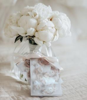 Bruiloft boeket van pioenrozen bloemen in een vaas staat op het bed van de pasgetrouwden met uitnodigingen