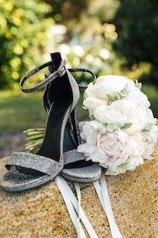 Bruiloft boeket van pioenrozen naast damesschoenen op een steen.