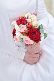 Bruiloft boeket van rode en roze rozen in de handen van de bruid close-up
