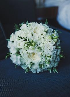 Bruiloft boeket van rode en witte rozen op de stoel