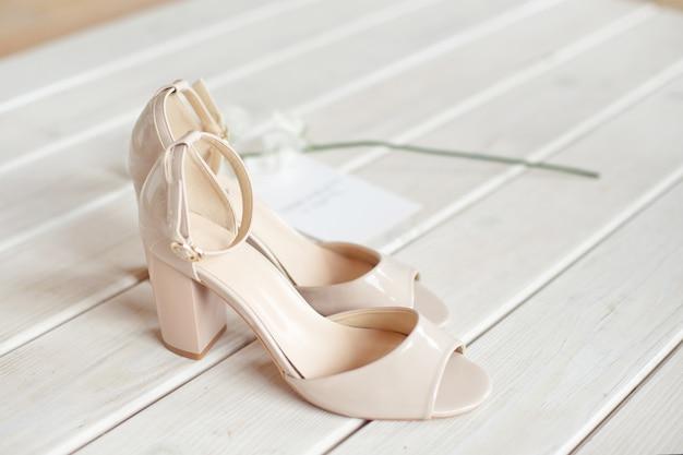 Bruiloft boeket van witte bloemen, schoenen en trouwringen op een houten tafel.