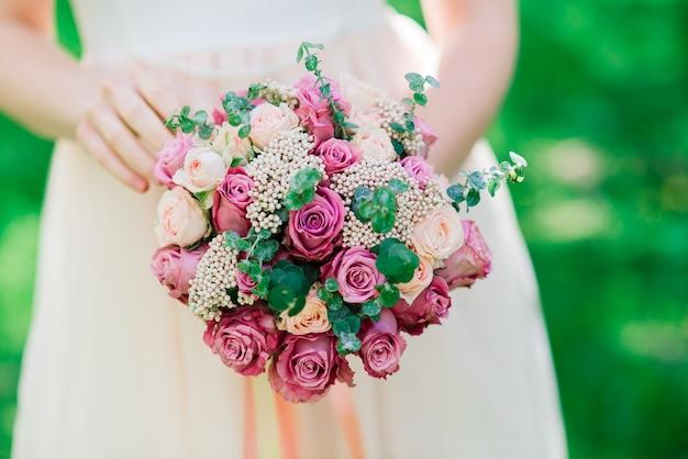 Bruiloft boeket van witte en rode rozen in handen van de bruid