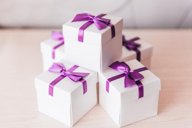 Bruiloft bonbonniere, witte dozen met paarse strikken