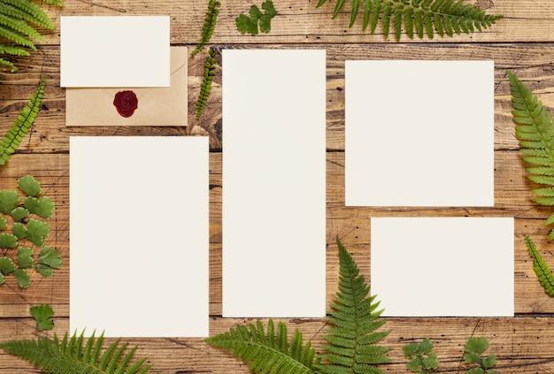Bruiloft briefpapier set kaarten en envelop versierd met varenbladeren bovenaanzicht op houten tafel. tropische mock-upscène met blanco papieren kaart plat gelegd