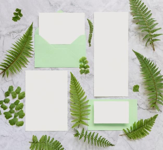 Bruiloft briefpapier set kaarten en envelop versierd met varenbladeren bovenaanzicht op marmeren tafel. tropische mock-upscène met blanco papieren kaart plat gelegd