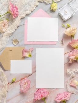 Bruiloft briefpapier set met envelop liggend op een marmeren tafel versierd met bloemen en linten