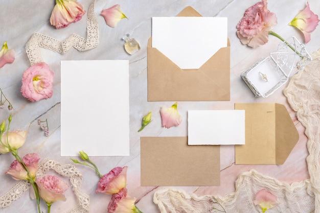 Bruiloft briefpapier set mockup met envelop op een marmeren tafel bloemen en linten