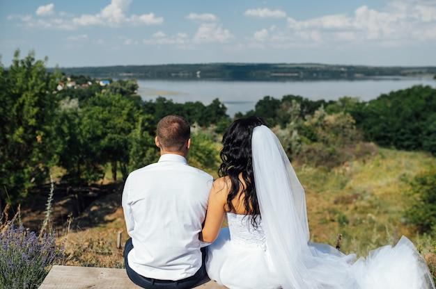 Bruiloft bruid en bruidegom op een bankje met natuurlandschap