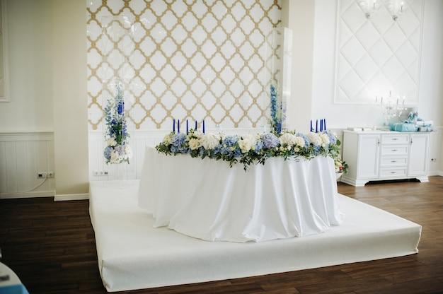 Bruiloft bruid en bruidegom tafel presidium versierd met veel bloemen