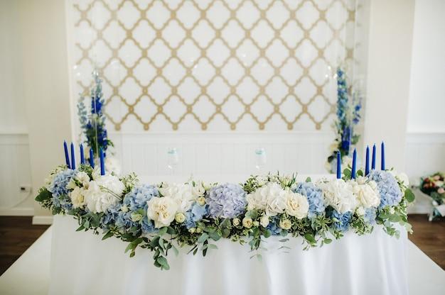 Bruiloft bruid en bruidegom tafel presidium versierd met veel bloemen.