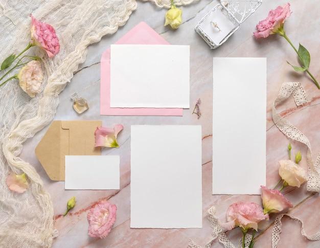 Bruiloft bruiloft briefpapier set met envelop liggend op een marmeren tafel versierd met bloemen