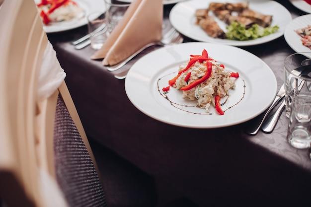 Bruiloft catering. witte keramische plaat met smakelijke salade met rode peper bovenop in close-up.