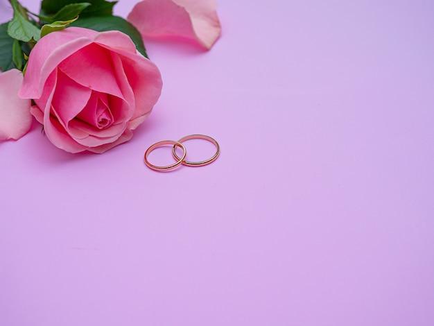 Bruiloft concept. mooie roze roos op roze achtergrond met twee trouwringen. kopieer ruimte.