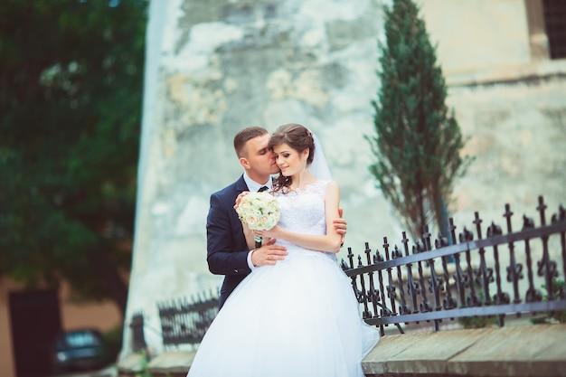 Bruiloft copule. mooie bruid en bruidegom. net getrouwd. detailopname. gelukkige bruid en bruidegom op hun bruiloft knuffelen. bruid en bruidegom in een park. trouwjurk. bruids bruiloft boeket bloemen