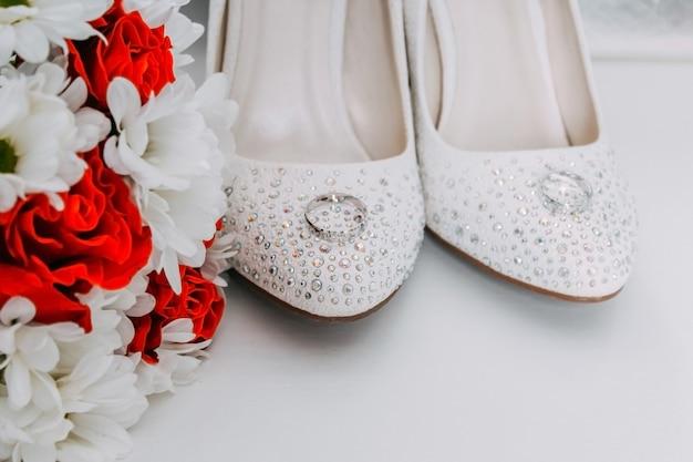 Bruiloft decor, details van de ochtend van de bruid. witte schoenen in strassteentjes en trouwringen