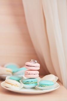Bruiloft decor. stijlvolle ringen van wit goud liggen op roze en mint bitterkoekjes