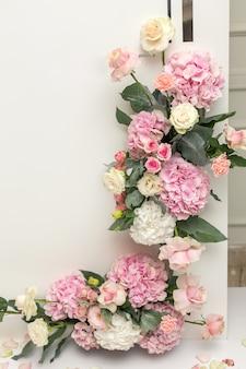 Bruiloft decoraties. de decoratievaas van de vakantie met verse bloemen dichtbij de huwelijksboog. roze rozen en anjers