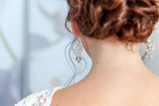 Bruiloft details en accessoires. bruid die pareloorring zet