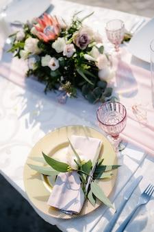 Bruiloft diner tafel receptie gouden plaat met roze stoffen servet en olijfbladeren framboos oud
