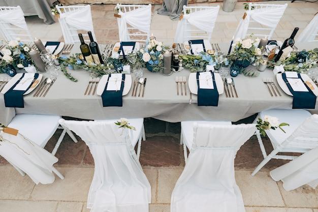 Bruiloft eettafel receptie een rechthoekige tafel met een grijs tafelkleed een bloemstuk met