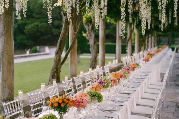 Bruiloft eettafel receptie een zeer lange tafel voor gasten met een wit gebloemd tafelkleed