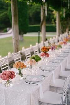 Bruiloft eettafel receptie een zeer lange tafel voor gasten met een wit tafelkleed bloemen
