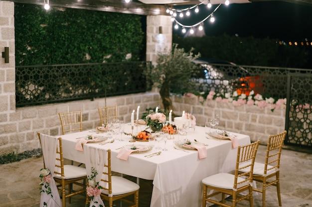 Bruiloft eettafel receptie rechthoekige tafel voor zes personen met een wit tafelkleed en roze
